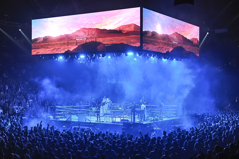 Stark looks on stage augmented by colorful video. 2017 Arcade Fire tour photo by Steve Jennings